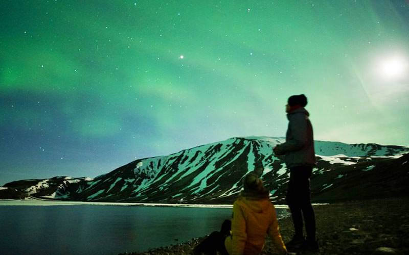 Two people looking out at the Northern Lights