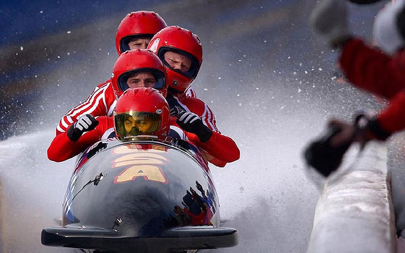 Some men on a bobsleigh in the snow
