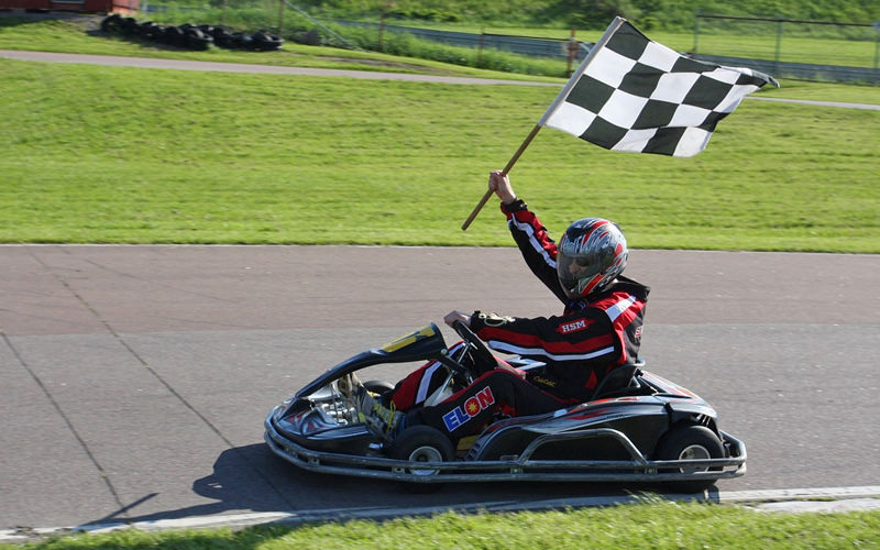 Someone riding in a go kart, waving a checkered flag