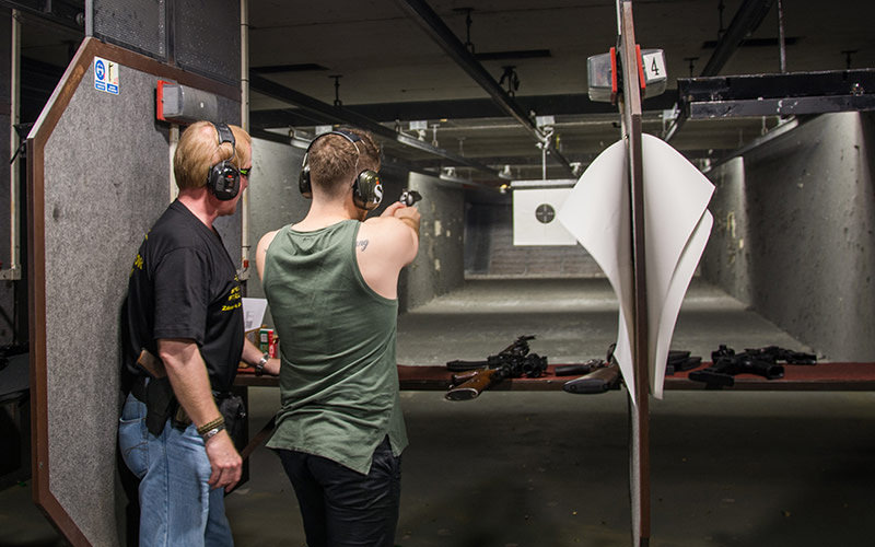 Two men in a shooting range wearing protective head gear and one aiming a gun at a target