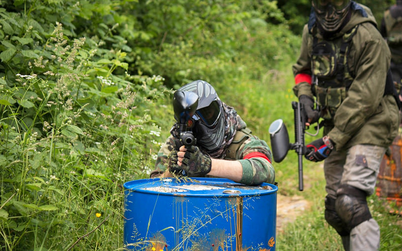 Two people wearing camouflage holding paintball guns