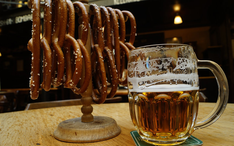 A pint of beer next to some pretzels