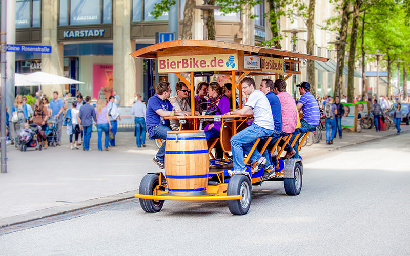 A group of men on a beer bike in a street