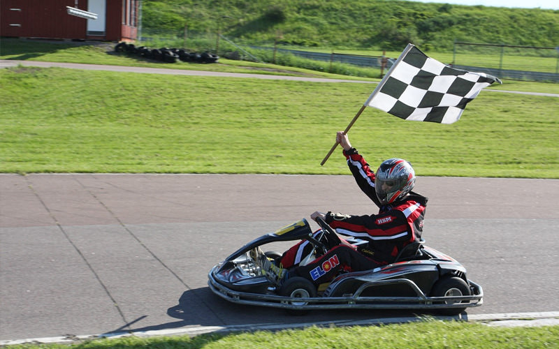 Someone driving a go kart waving a checkered flag in the air