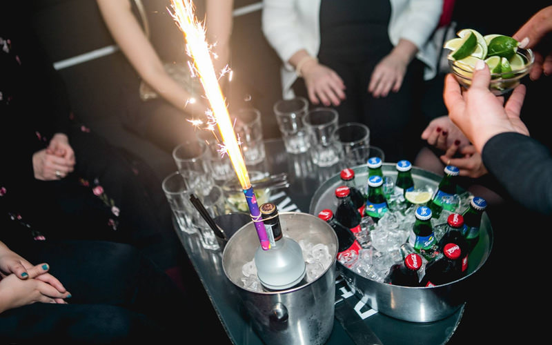 A table with two ice buckets and various drinks in them, along with a sparkler