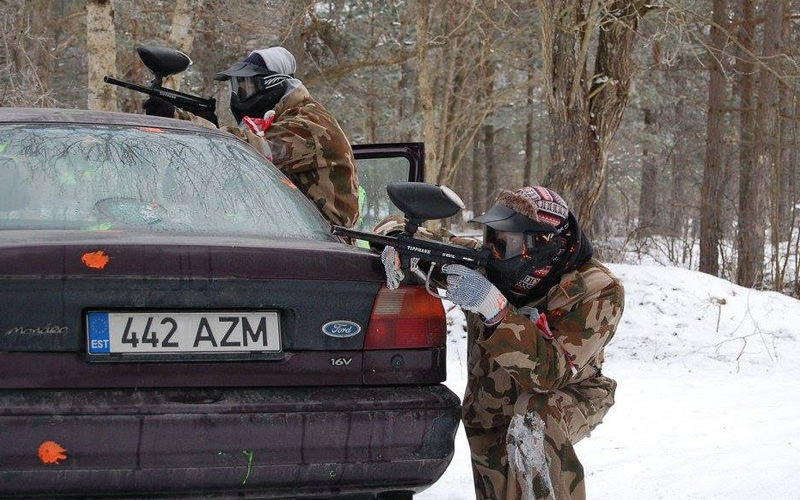 Two people dressed in camouflage hiding behind a car and carrying paintball guns