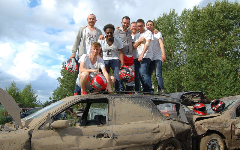 A group of people stood on top of a vandalised car