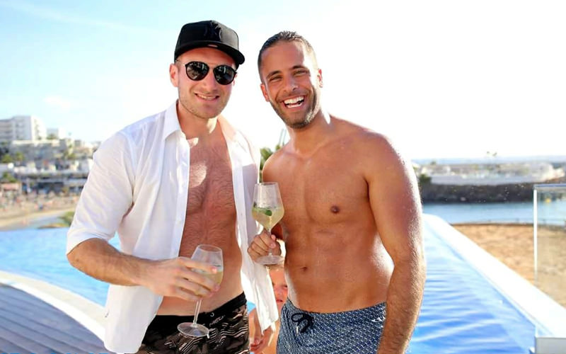 Two men holding drinks with a swimming pool and beach in the background