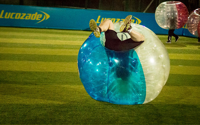 Someone on a pitch upside down in an inflatable zorb