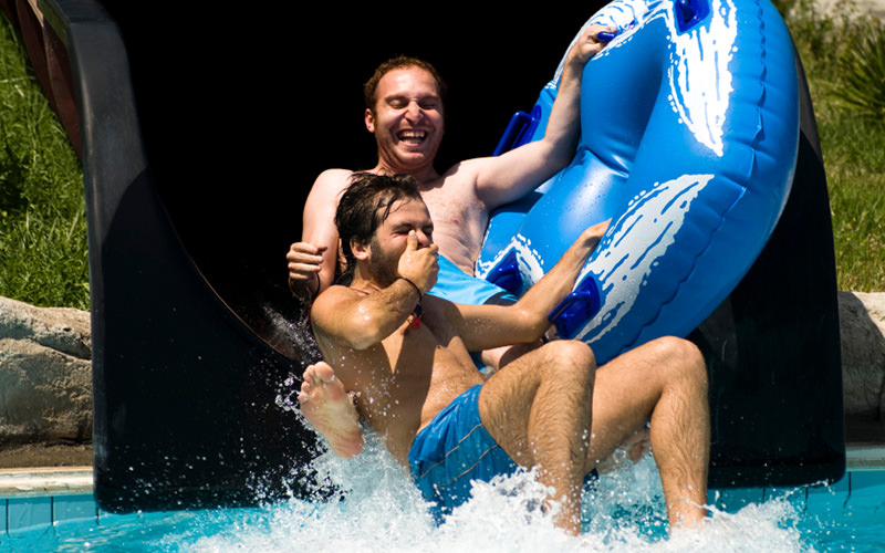 Two men coming out of a water slide