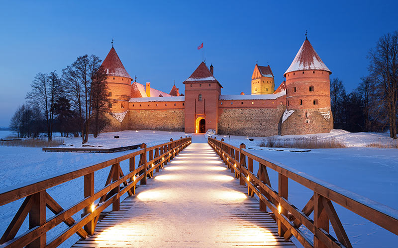 A bridge leading to a castle, with snow on the ground
