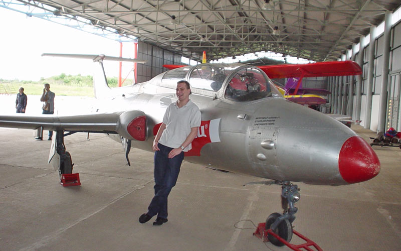 A man leaning on an aircraft in a hanger