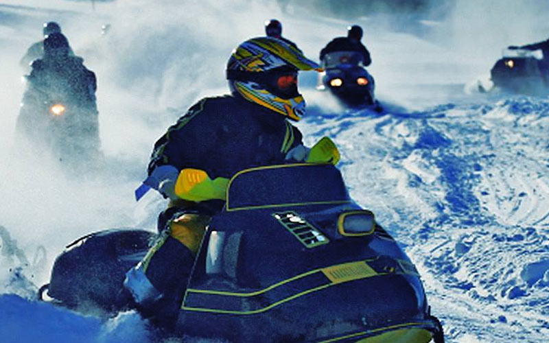 A group of people on snowmobiles