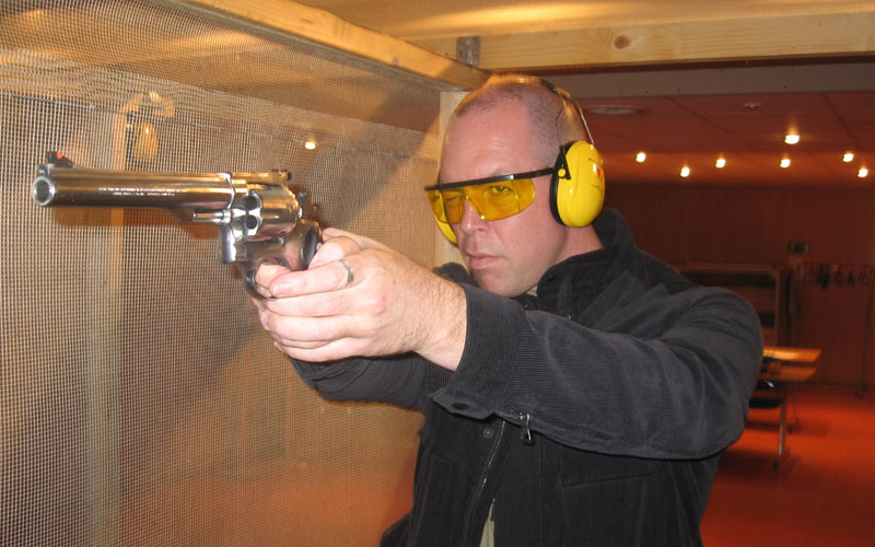 A man wearing protective ear guards aiming a gun