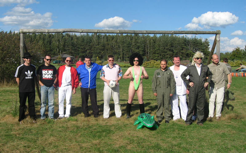 A group of men stood in front of a football goal outside, with one dressed in a green mankini