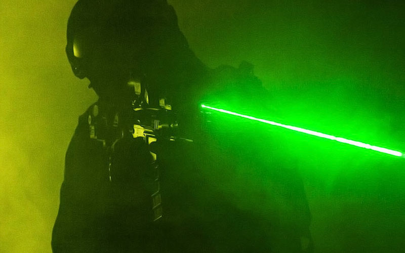 Someone pointing a laser gun with a green laser beam coming out of it