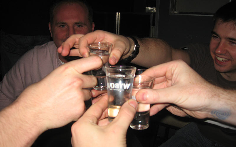 A group of men cheering with shots