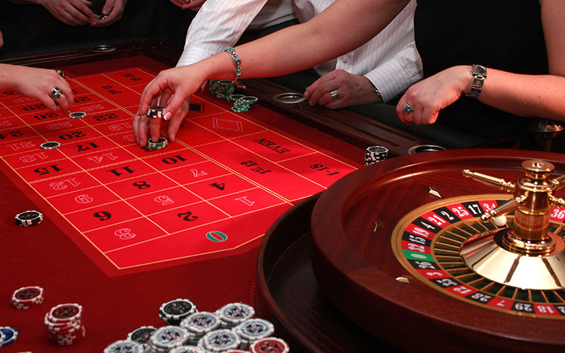A close up of a roulette wheel and a table, in a casino