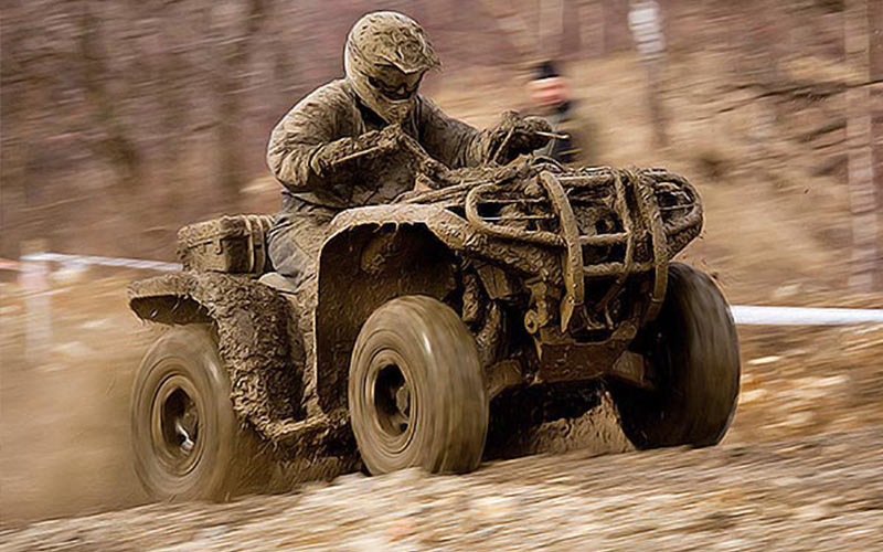Someone riding a quad bike, covered in mud