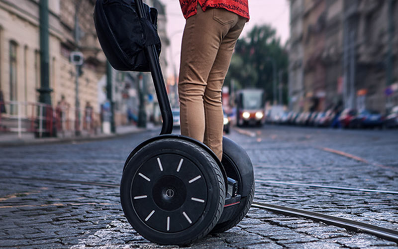 A close up of someone on a segway in a street