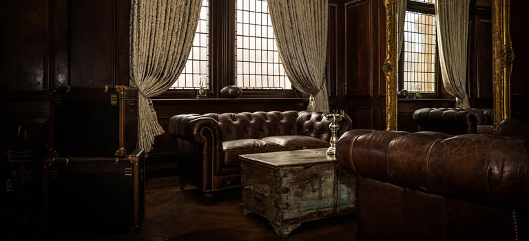 A dark room with leather sofas