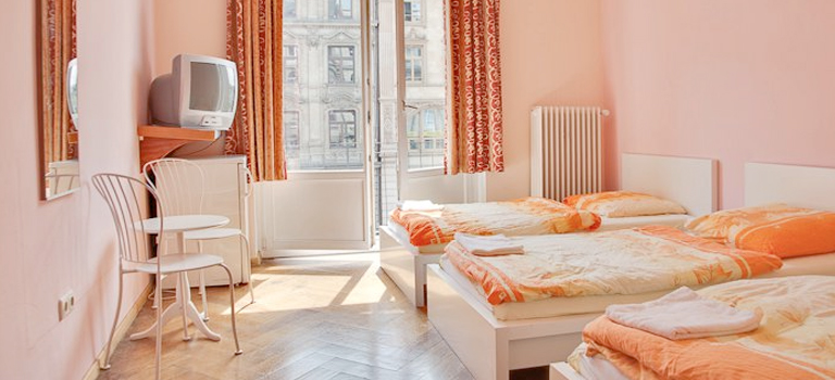 Three beds sit in a light and airy hotel room, overlooking the streets of Frankfurt.
