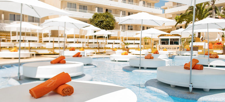 Some white sun loungers with parasols and orange towels on them