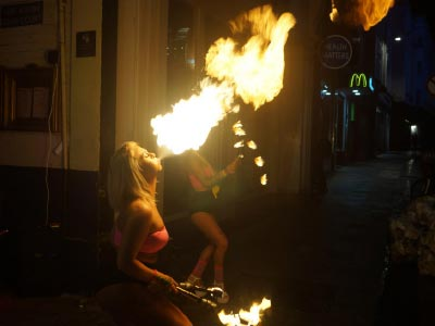A woman blowing fire in a bar