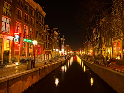 A canal illuminated at night in De Wallen
