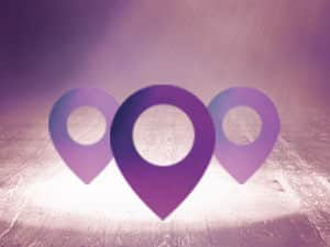 Three purple map pins in the spotlight with a purple background