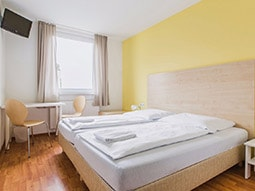 Two single beds in a yellow room, with a bedside table in the foreground