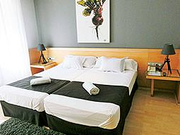 Two single beds topped with towels and green throws, with bedside tables at either side