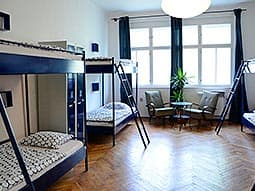 Two bunk beds in a dorm hostel room, with tables and chairs at the back of the room