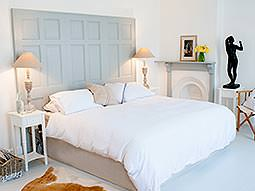 A double bed with duckegg headboard and various ornaments around the bedroom
