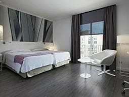 Two double beds in a hotel room at Hotel NH Barcelona Stadium