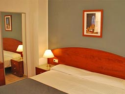 A double bed in a hotel room, with a mirror and bedside table in the background