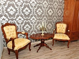 Some old fashioned furniture against a paisley print wall