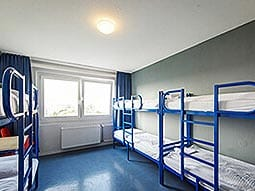 Some bunk beds in a room with a blue floor and large window