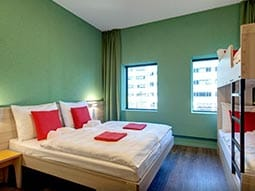 A dorm room with green walls and white and red bedding