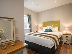 A spacious double bedroom with a lime and grey colour scheme and runners on the bed