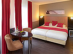 A hotel room with a double bed, table and two chairs