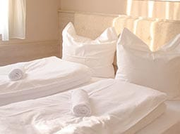 Close up of two single beds with towels rolled up placed on each bed