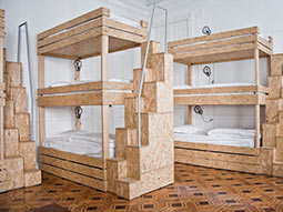 Some modern wooden bunk beds in a white walled room
