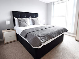 A light room with a black and white double bed and a large window