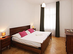 A double bed and some furniture in a room with white walls and green curtains