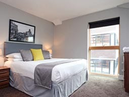 Image of a room with a double bed with a grey bed runner and grey and yellow cushions with a big open window