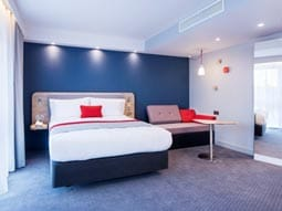 Image of a room with a double bed with blue walls and grey carpet with red cushion
