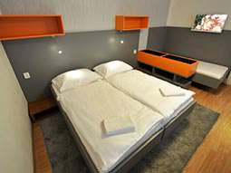 Image of a room with two single beds pushed together with white bedding and grey headboards and orange shelving units and another single bed at the other end of the room with a flat screen tv on the wall