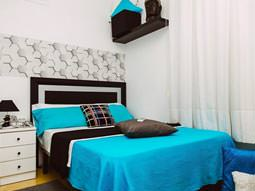 Image of a room with a double bed with turquoise and black bed sheets and white furniture with white floor length drapes and a black and white head board