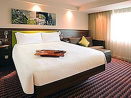 A white double bed with a city skyline picture above the bed, with a brown leather sofa to one side of the bed